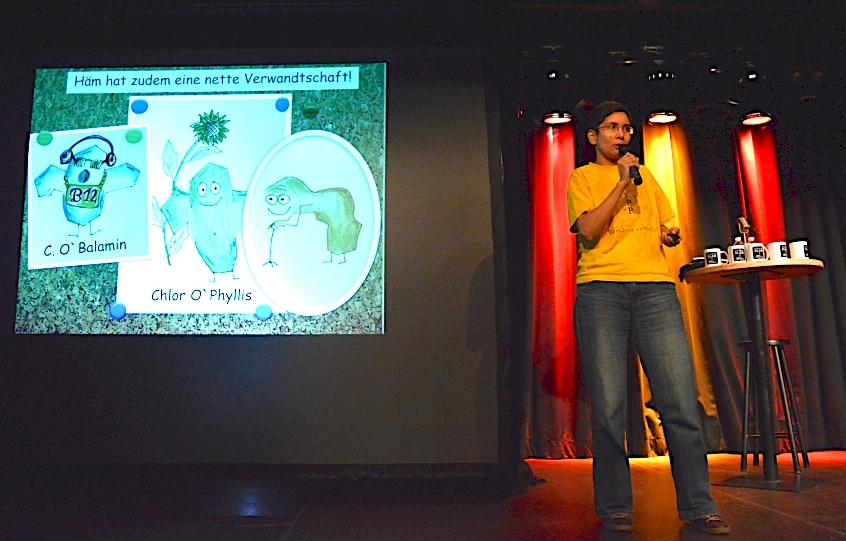 Eine Frau mit einem gelben T-Shirt auf einer dunklen Bühne. Auf einer Leinwand sind Skizzen von biologischen Zellen zu sehen.