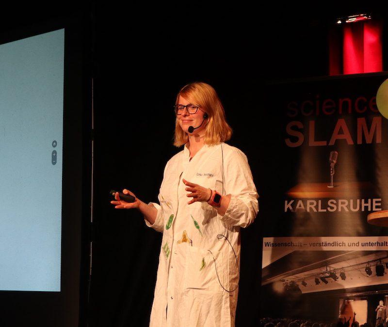 Eine Frau steht in einem weißen Laborkittel mit aufgemalten Bakterien auf einer dunklen Bühne
