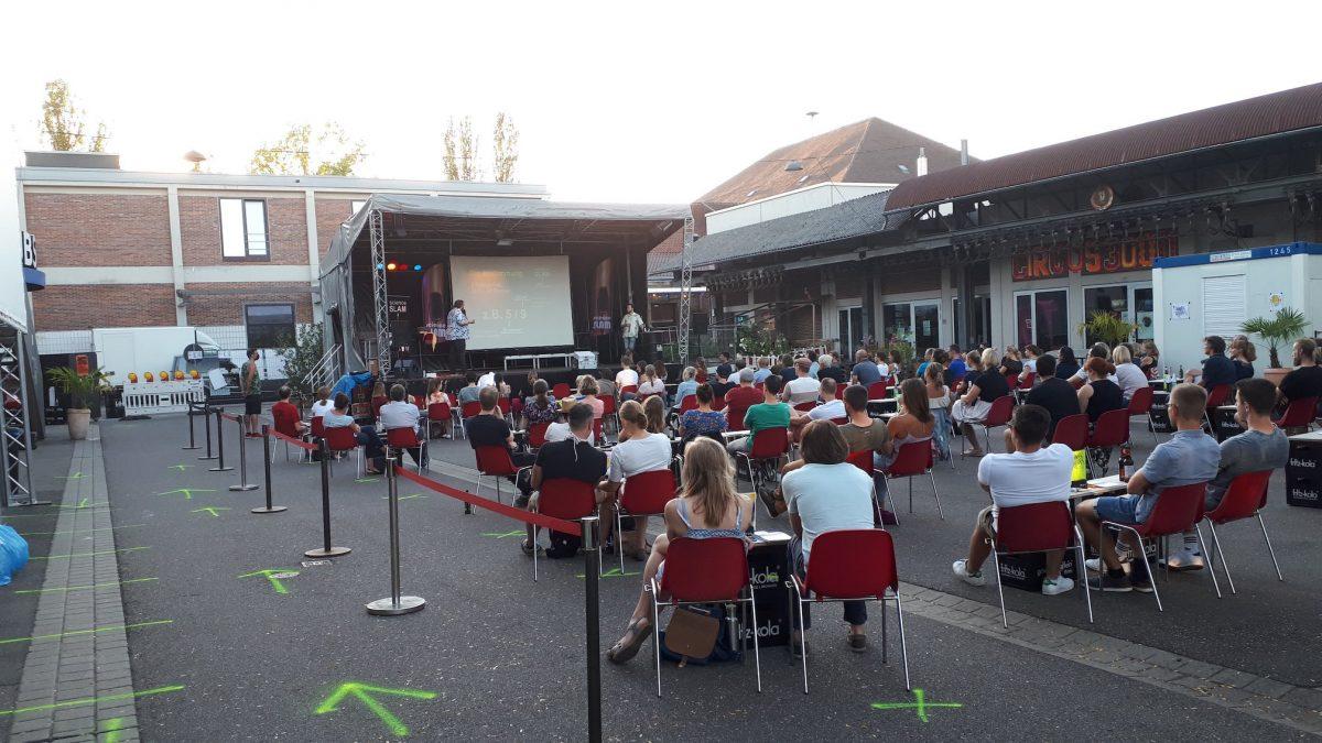 Eine Outdoor-Bühne, davor sitzen Menschen.